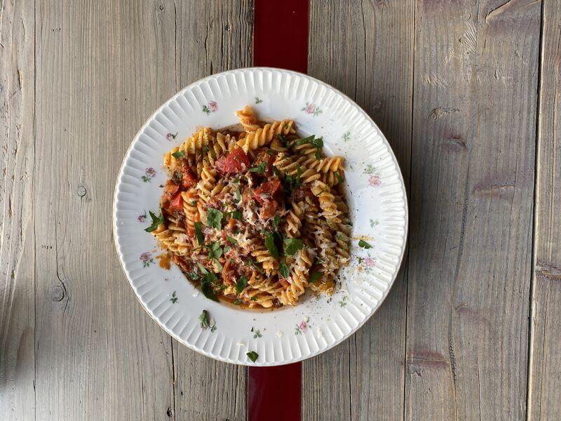 Pasta mit einer Tomaten-Bolognese, verfeinert mit Zwiebeln, Paprika, Möhren, Knoblauch und Sellerie, abgeschmeckt mit Rotwein