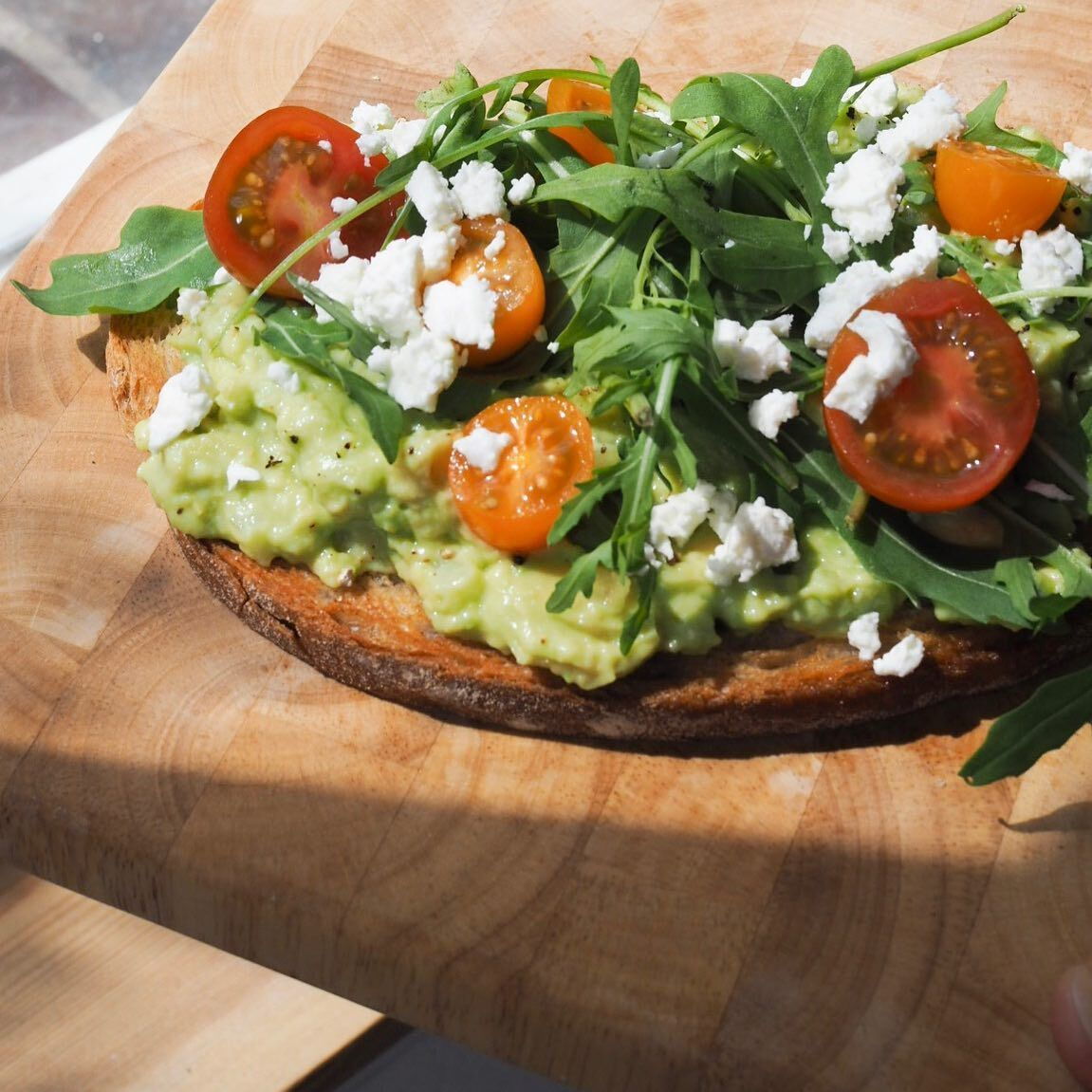 Smashed avocado toast with feta and cherry tomatoes