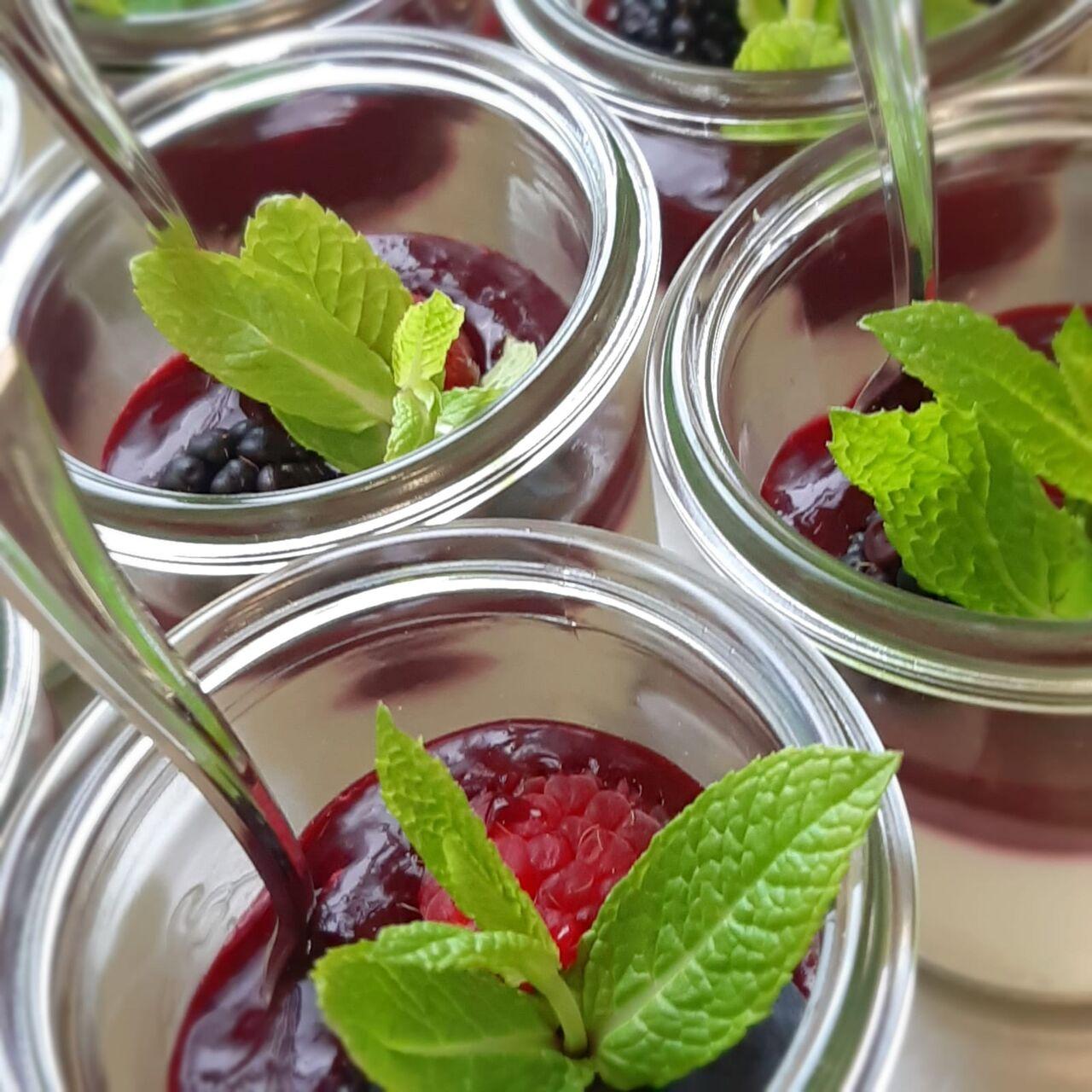Ein sahniger Nachtisch im Glas, darauf eine fruchtige Schicht aus frischen Waldfrüchten