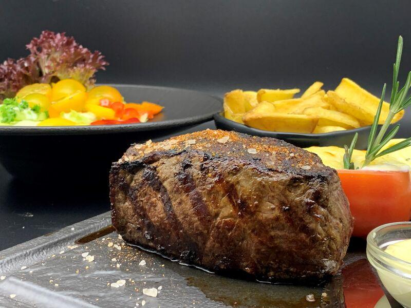 300g argentinisches Black Angus Striploin (Rumpsteak) mit hausgemachter Kräuterbutter, Steakhouse Fries und einem Salatteller