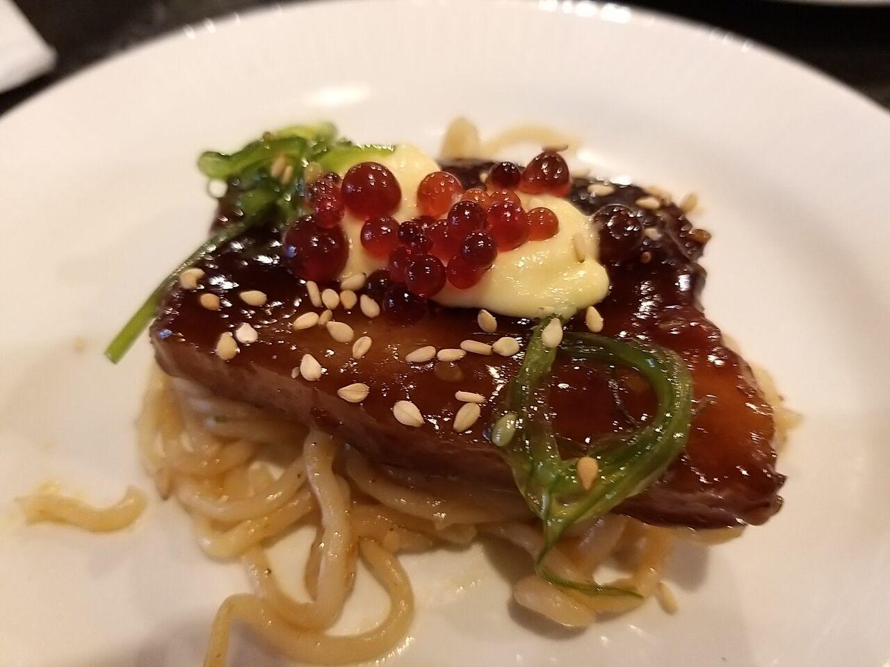 Tapa de panceta asada a baja temperatura con fideos kimchi, alga wakame, alioli cítrico y perlas de vermú macerado con fresas
