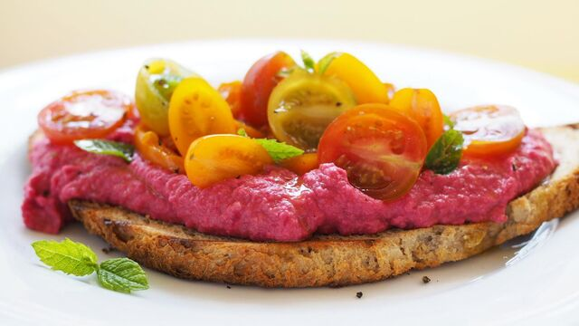 Vegan beetroot hummus toast with slow cooked peppers, cherry tomatoes and mint