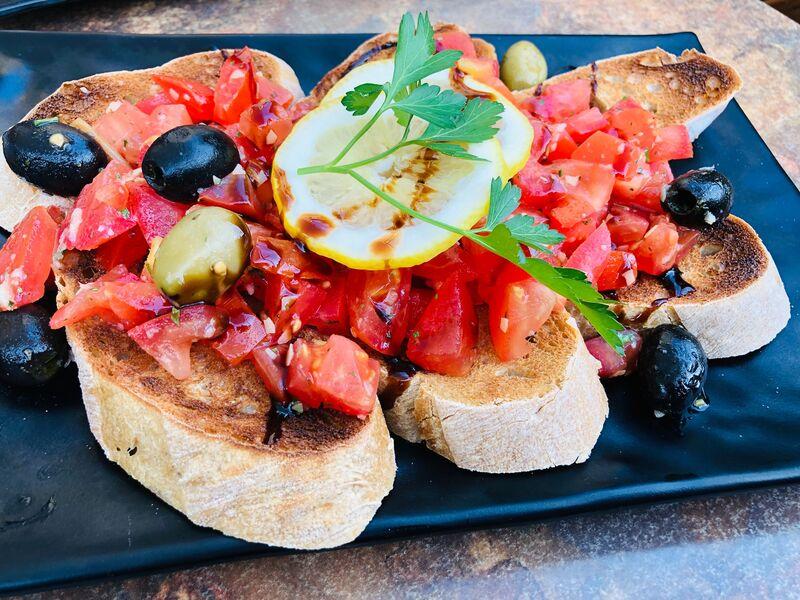 Bruschetta. Tomatenwürfel fein gewürzt mit Oliven und frischen Kräutern auf knackig geröstetem Ciabatta