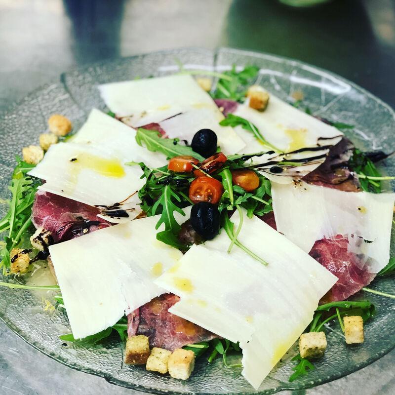 Rindercarpaccio auf rucola mit frische Champignons e Parmesan Blätter.