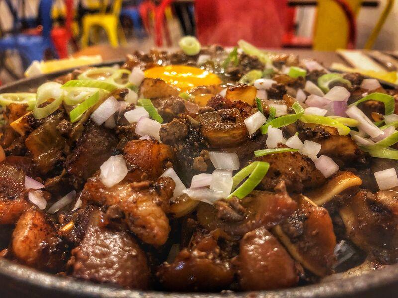 SIZZLING SISIG Orejas y hígado de cerdo salteado en mantequilla y cebolla, servido en plato de hierro fundido con huevo.